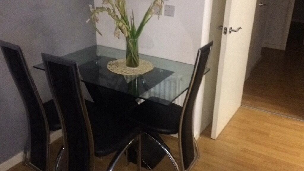 """Glass top dinning table with black """"x"""" shaped legs. Three black and stainless steel chairs."""