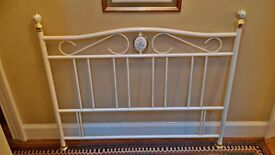 Double divan bed with Victorian style headboard with brass knobs.