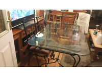 glass topped heavy wrought iron table & 6 chairs
