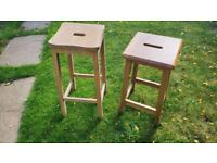 A pair of wooden lab stools