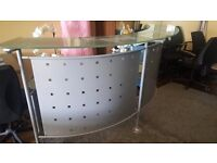 Reception desk with glass top and steel surround