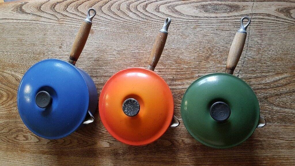 Three Le Creuset saucepans with lids.