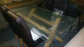 A brand new glass topped dining table with 6 chairs.