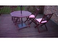 A round brown garden table with three chairs
