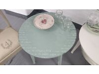 Shabby chic, round coffee table with a shelf below in duck egg colour.