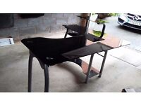 Black glass computer table. Good condition. Swivel workspace which extends working space if needed