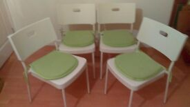 Four white plastic and metal chairs