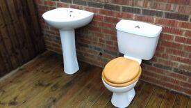 Toilet, sink and pedestal matching set.