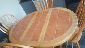 Kitchen/dinning extendable table and 4 chairs. Tiled top .