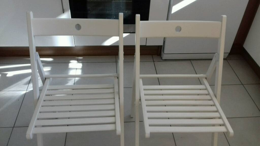 2 foldable white chairs