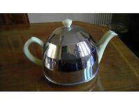 A yellow ceramic teapot with a chrome isulated cover