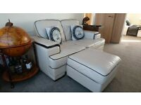Cream leather 2 seater sofa and footstool.