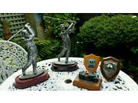 Lot of golf trophies and 1 car trophy