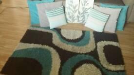 Teal/brown rug, cushions, wall art