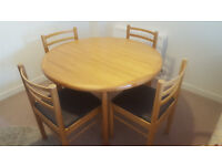 Wooden, circular extending dining table and four chairs. Good condition