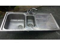 stainless steel kitchen sink with taps and dual plugs in good condition