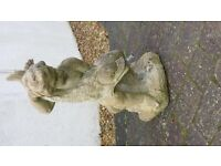 Classic garden sculpture of boy holding fish