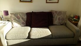 3 seater material couch with purple cushions