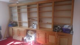 Built in wooden shelves and cabinets running full length of the wall