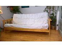 Hardwood sofa bed with cream cushions