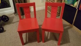 2 little red childrens chairs