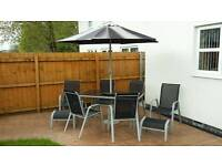 Garden table with 6 chairs, 2 footstools and parasol