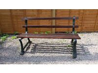 AN ANTIQUE GARDEN BENCH (ORIGINALLY A RAILWAY BENCH) WITH CAST IRON SIDES AND WOODEN SLATS