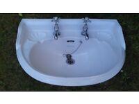 White ceramic bathroom basin (shell design) with vintage taps