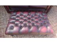 A large ox blood red leather Chesterfield footstool