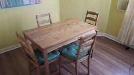 Pine wood table and 4 chairs with cushions, in good to excellent condition