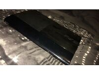 PlayStation 3 console with games and controllers