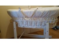 White wicker moses basket on rocking stand
