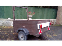 Wooden trailer 4ft x 3ft on - metal chassis. Old, but serviceable.