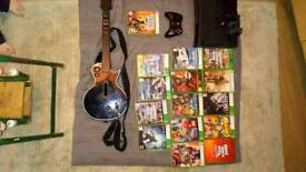 Xbox with games, controllers and guitar.