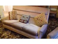Three piece suite (three seater settee, two armchairs) in beige velour.