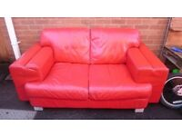 Red two seater leather sofa in great condition. Been in playroom for a few years.