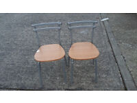 2 grey metal framed chairs with light wood seats