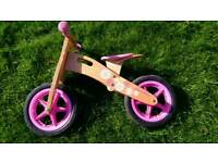 Pink wooden balance bike