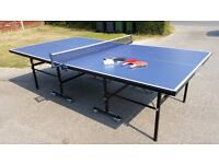 Table tennis table folds away for storage with bats