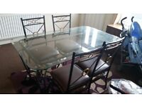 Beautiful heavy glass dining table and chairs. Chairs cover is brown leather