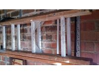 Old but sturdy and still fully usable double extension wooden ladder with aluminium treads
