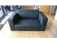 Almost new, hardly used, black faux leather two seater sofa