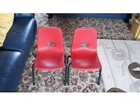 Childrens red stackable chairs (two).