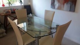 Adjustable glass dining room table 4 matching cream highbacked chairs
