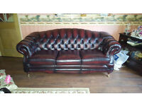 ANTIQUE RED LEATHER CHESTERFIELD CONSISTS OF 3 SEATER,2 CHAIRS AND MACHING STUDDED LEATHER TABLE