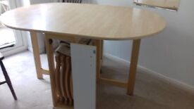 Modern drop-leaf dining table with four folding chairs which stow away inside table