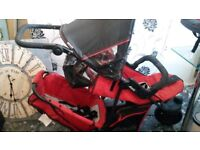 Red and black double pram with raincover
