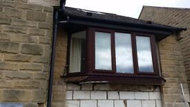 Brown UPVC Double Glazed Bay Window. White Interior with brass colour handles.