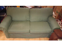 A fully functional green two seated sofa (can sit three) Some slight damage.