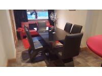 Glass dining table and 6 chairs . Hardly used